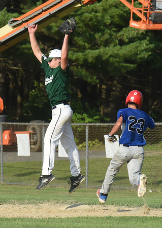 BRYAN EATON/Staff photo. Pentucket first baseman Chase Dwight jumps for the throw as Georgetown's Carter Lucido is safe.