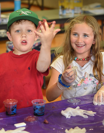 "BRYAN EATON/Staff Photo. Pippa Hattersley, 8, left, smiles as five year-old Anders Yunghans' slime he created is a little slimier than it's supposed to be in Crazy Chemworks at Amesbury's Cashman School, a summer program by Amesbury Youth Recreation.""Galaxy Grace"" of Mad Science in Boston was teaching youngsters about chemical reactions, states of matter and other fun, hands on science."
