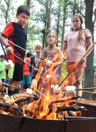 BRYAN EATON/Staff Photo. Using long sticks, youngsters roast some marshmallows after they did the same to hot dogs at Amesbury Youth Recreation's Camp Kent Nature Center for Wilderness Week. They learned about raft and shelter building, studying aquatice life around Lake Gardner and got in hiking and canoeing as well.