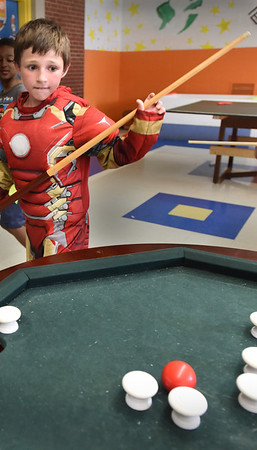 BRYAN EATON/Staff Photo. Alex Chernick, 8, looks at his next shot in a game of bumper pool while dressed as Iron Man at the Boys and Girl's Club in Salisbury. It was Holiday Week and there were celebration Halloween complete with a costume contest.