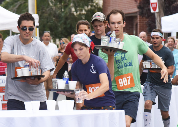 BRYAN EATON/Staff Photo. Contestants, including winner Leanne Paparella of Anchor Deck Stone Pizza, center, set glasses of water down on tables.