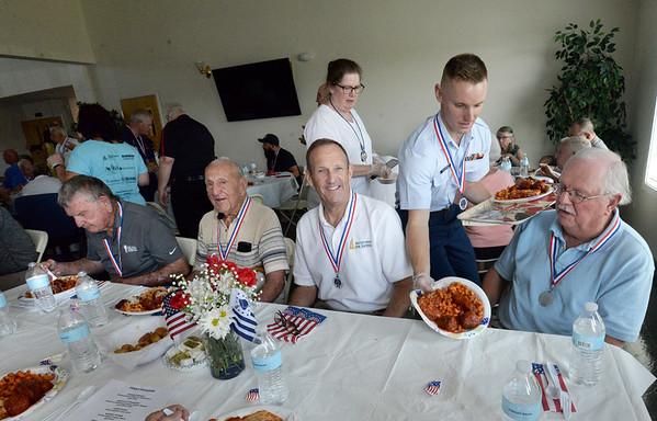 "BRYAN EATON/Staff Photo. U. S. Coast Guard fireman Curtis Williamson helps serve dinner to veterans, from left, Jack Welch, Newburyport; Robert ""Boots"" Chouinard, Salisbury; Chris Sullivan and Bob Cielinski, both of Newburyport."