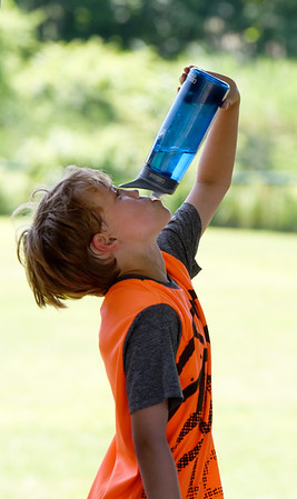 BRYAN EATON/Staff Photo. Wesley Young, 8, takes a long sip of water after playing games at the Newburyport Youth Services' Clipper Kids Camp at Perkins Park. Lots of water sports and games will be played this week as the temperatures are to rise.