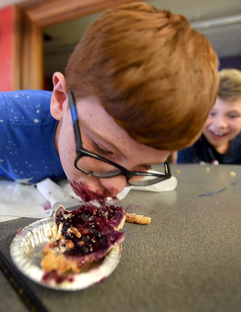 "BRYAN EATON/Staff Photo. John McGinn, 9, tries to pull the blueberry pie out the tin at the Boys and Girls Club in Salisbury on Monday afternoon. The Pie Eating Contest was part of their ""Ooey Gooey"" week theme."