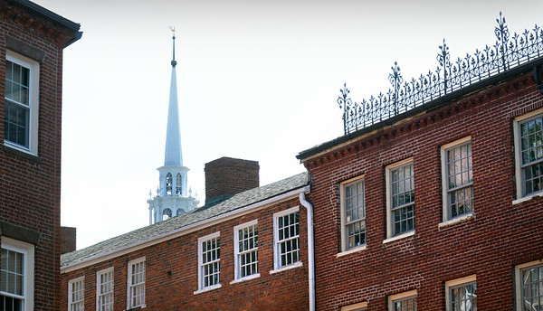 BRYAN EATON/Staff Photo. The steeple of the Unitarian Church on Pleasant Street in Newburyport looms over the iconic brick buildings on Inn Street before the storms came through on Wednesday afternoon.