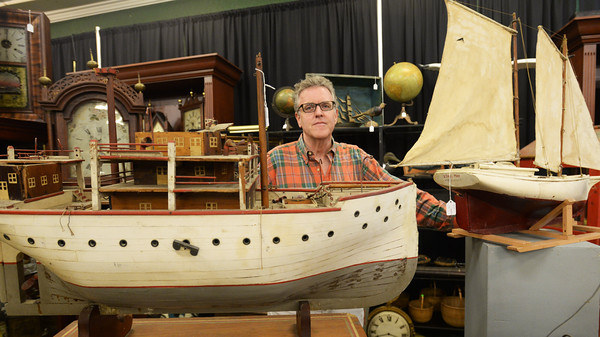 BRYAN EATON/Staff Photo. Dan Meader behind a replica of the Nantucket Lightship, one of many, many items up for auction from the estate of William Johnson of Kennebunk.