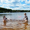 BRYAN EATON/Staff Photo. Cousins Ava Cronin, 10, left, and Leah Paradis, 6, both of Haverhill play at Lake Gardner Beach in Amesbury after visiting an aunt on nearby Whitehall Road. The weekend's weather is looking very summer like with lots of sun and warm temperatures especially for Father's Day.