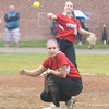 JIM VAIKNORAS/Staff photo Amesbury pitcher Hayley Catania ducks as teammate Adrienne Harris throws out a runner against Mount Alvernia at Chris Perry Field in Amesbury Sunday. The Indian's won the game 9-2.