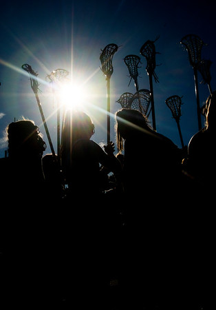 JIM VAIKNORAS/Staff photo Newburyport's girls lacrosse team raise their sticks before the State semi-final game  against Norwell at Babson College Tuesday night.