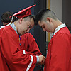 JIM VAIKNORAS/Staff photo Kenneth Williams helps fellow graduate Meteo Wirzburger with his sash as they get ready inside Amesbury Middle School to march in to Landry Stadium Friday night.
