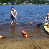 BRYAN EATON/Staff photo. Spencer Butzen of Amesbury and his fellow lifeguards, including Helena Entrican of Amesbury, set up the buoy markers at Lake Gardner Beach on Tuesday, dropping cinder blocks from a paddle board to anchor them in place. They begin duty watching bathers on Saturday which is timely as temperatures will be in the 90's for the weekend.