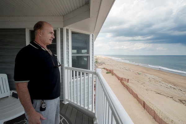 JIM VAIKNORAS/Staff photo Tom Saab looks out from one of his rental properties on Salisbury Beach.