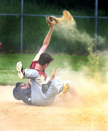 JIM VAIKNORAS/Staff photo Newburyport's Thomas Murphy throws up some dirtafter tagging Essex Tech player Andrew Fournier out as he attempt to steal second during heir game Saturday in Newburyport. The Clippers won the game 3-0,
