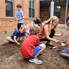 BRYAN EATON/Staff photo. Bresnahan School STEM teacher Kristin Spinney works with students as they plant pumpkin seeds a the entrance to the Newburyport School.