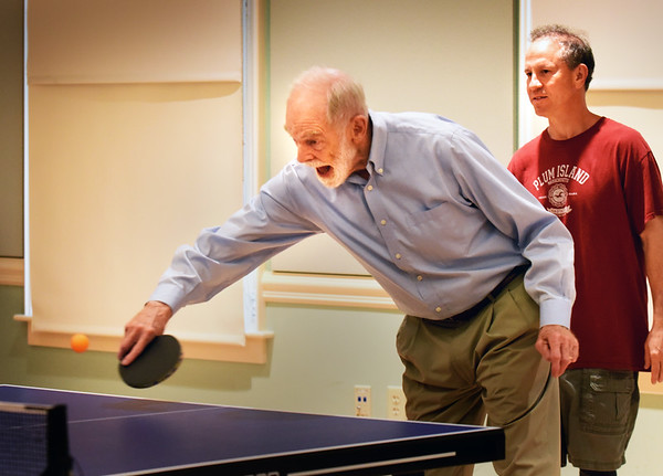 BRYAN EATON/Staff photo. Edwin Lynn of Ipswich connects with a volley as he and Andy Morris, of Newburyport, right, take on Bruce Merluzzi of Salisbury and Steve Clinard of Newburyport in a game of ping pong. The activity at the Newburyport Senior Center has grown with another table being added to accomodate the players which meet on Tuesday and Friday afternoons.