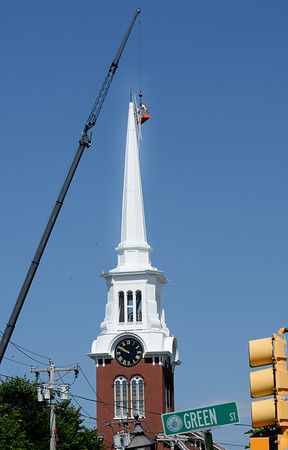 BRYAN EATON/Staff photo. Two workers on a platform hanging from a crane make final repairs to the steeple of the Central Congregational Church in Newburyport.