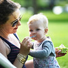 BRYAN EATON/Staff photo. Amanda Roberts gives her daughter, Penelope, some ice cream on Newburyport's Waterfront Park on Monday afternoon once the sky turned blue. The toddler, who turned one on Sunday and like to smile for the camera, and mom were visiting from Georgetown.