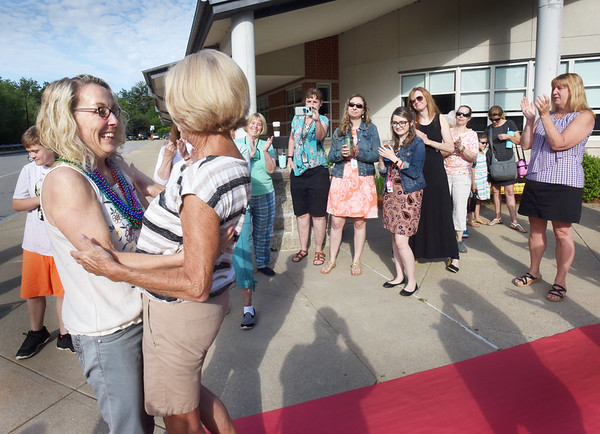 BRYAN EATON/Staff photo. Michelle Howard is greeted by her mother, Marie Roy, as fellow teacher applaud.