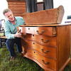 BRYAN EATON/Staff photo. Dan Meader of McInnis Auctioneers shows off a dresser built in Newburyport in the late 1700's by Joseph Short. On top is a bread trough in which bread was made on the ship Mary and John, the first to come up the Parker River in 1635.