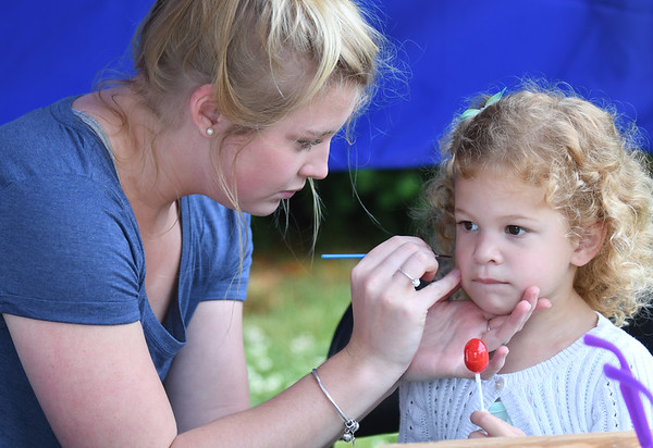 JIM VAIKNORAS/Staff photo Eleanor D'Ambnoso,4, holds her lolipop as Miriam Swartzentruber paints a rainbow on her face at the Amesbury Day's Block Party Thursday Night a the Main Street Congregational Church.