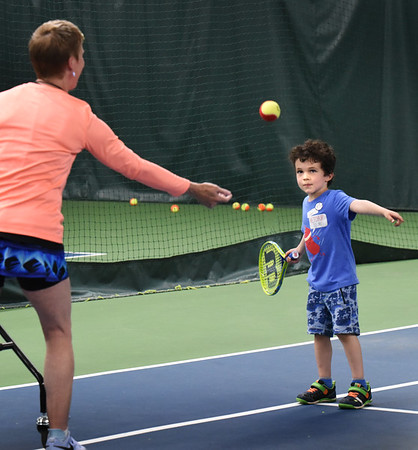 BRYAN EATON/Staff photo. Connor Sands, 5, of Newburyport practices his eye-to-hand coordination as Hillary O'Connor tosses the tennis balls.