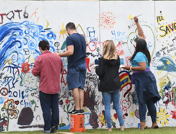 JIM VAIKNORAS/Staff photo People gather to paint messages on a free standing wall at the Byfield Music and Arts Festival Saturday.