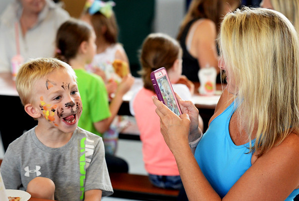 BRYAN EATON/Staff photo. Jace Landry, 6, of Amesbury, makes a leopard scowl, as he had his face painted that way, as his mother, Lisa, takes a photo.