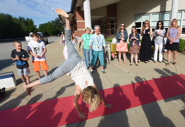 BRYAN EATON/Staff photo. Howard does a cartwheel on a red carpet fellow staff members laid out.