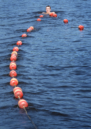 BRYAN EATON/Staff photo. Spencer Butzen of Amesbury and his fellow lifeguards set up the buoy markers at Lake Gardner Beach on Tuesday, dropping cinder blocks from a paddle board to anchor them in place. They begin duty watching bathers on Saturday which is timely as temperatures will be in the 90's for the weekend.