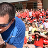 "BRYAN EATON/Staff photo. Salisbury Elementary School Principal James Montanari kisses a baby pig at the start of Field Days on Thursday morning. If students did enough reading during a recent read-a-thon, he said he would do something crazy. The students decided for a kiss of a pig, followed by riding a unicycle and third by getting ""slimed."""