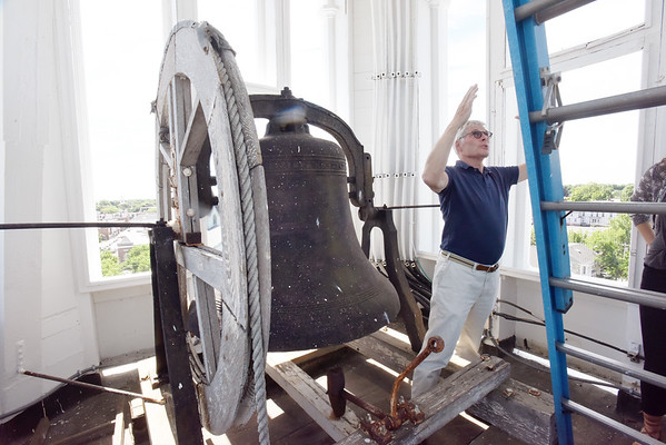 BRYAN EATON/Staff photo. Jim Robins describes the repairs made to the steeple over the past year.