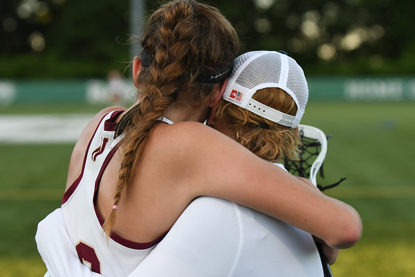 JIM VAIKNORAS/Staff photo Newburyport coach Catherine Batchelder consoles Margaret Cote after the Clippers 14-11 lose to Norwell in the State semi-final game at Babson College Tuesday night.
