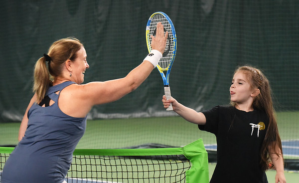 BRYAN EATON/Staff photo. Bentlee Dragon, 5, of Salisbury gets a high five from instructor Joni Stone after making several good volleys.