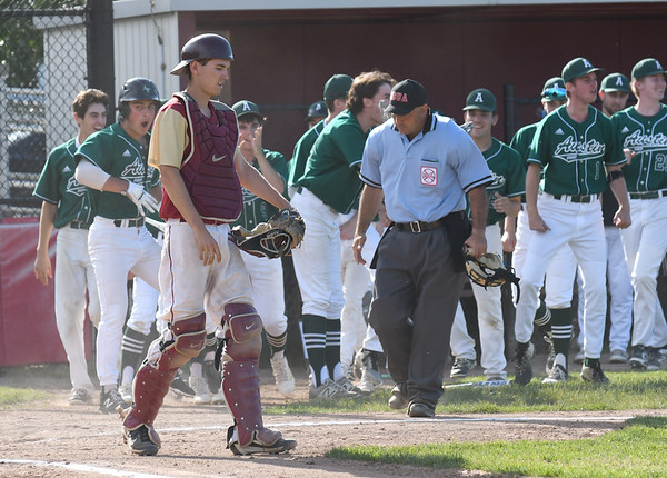 JIM VAIKNORAS/Staff photo Austin Prep player celebrate a 1st inning grand slam as  Newburyport catcher Kenny Hodge walks past home plate during their game at Melrose high Sunday afternoon.