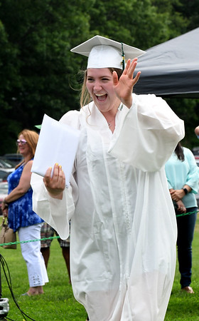 JIM VAIKNORAS/Staff photo Pentucket graduating senior Shannon Twomey waves after getting her diploma at the school Saturday morning.