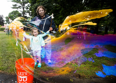 JIM VAIKNORAS/Staff photo Liv Mahan , 2, and her grandmother Melissa Vesper make giant bubbles at a fund raiser for the stone tower at Atkinson Common in Newburyport Saturday. The event featured a beer garden, Beatles music, a food truck, games, and classic cars.