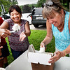 BRYAN EATON/Staff photo. Amesbury Middle School science teacher Gale Regis, right, and teaching assistant Violeta Clancy, scoop Hodgies Ice Cream as fast as they can during Monday's hot weather. They were helping out at sixth-graders end-of-year celebration at the Amesbury Town Park.