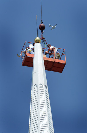 BRYAN EATON/Staff photo. Workers prepare the steeple of the Central Congregational Church in Newburyport for the return of the weathervane as a plane passes by.