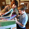 BRYAN EATON/Staff photo. Harry Meure, 10, of Newbury and his family donated several books of sheet music in this box, one of several headed to a composer in Albania.