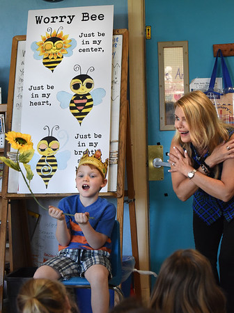 BRYAN EATON/Staff photo. Aren Bloom, whose birthday was Wednesday, raises the sunflower on queue as he helps author Ann Biese lead students in breathing excercises at the Page School in West Newbury.