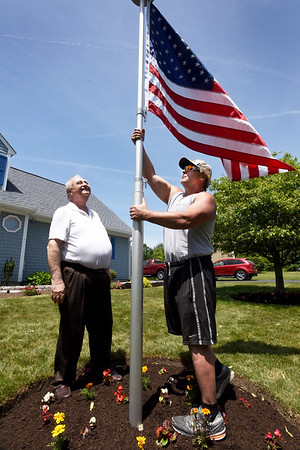 BRYAN EATON/Staff photo. Vietnam veteran Ed Power, left, watches as his landscaper of 20 years, Mike Beaton, sets up a telescopic flag pole. Power has had a flagpole on his property since he bought the home at Quail Run Hollow in Newburyport over 30 years ago. The old pole was in disrepair and he ordeded this new one that doesn't need a rope to hoist and Beaton, himself a veteran, offered to install it for him.