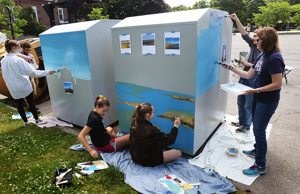 BRYAN EATON/Staff photo. Newburyport High School and Pentucket Regional High School art students have joined forces to decorate deposit bins for books, cd's and dvd's at Cushing Park. Area scenics like the Plum Island Light are being painted.