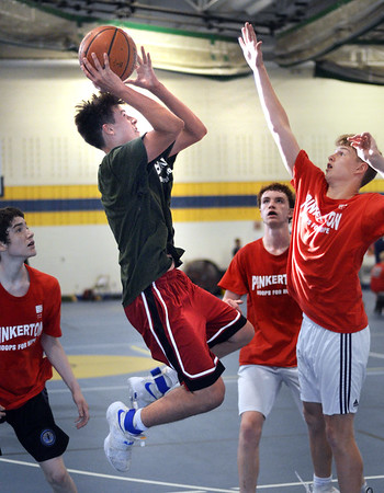 CARL RUSSO/staff photo. NEWBURYPORT NEWS: Pentucket's Peter Cleary sails to the hoop against Pinkerton's Andy MacDonald. Pentucket defeated Pinkerton in boys Hoops for Hope action Thursday night. 6/21/2018