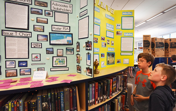 BRYAN EATON/Staff photo. Molin Upper Elementary students Kyle Lisauskas, left, and James Moore, both 10, check out civic engagement displays on work done my Nock Middle School students. One on the left was by Cassidy Anderson on beach pollution, and the right, the opiod crisis by Sydney Turner.