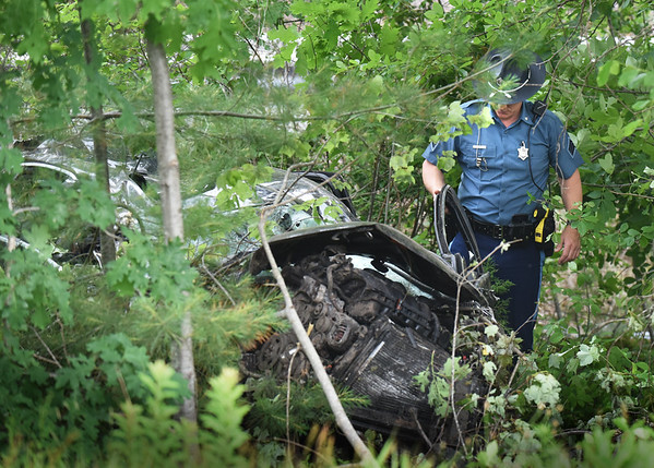 BRYAN EATON/Staff photo. A Massachusetts state trooper checks out a car that went off the road at the offramp to the Maria Miles Rest Area on Interstate 95 in Salisbury early Monday afternoon. The woman who was driving was thrown from the vehicle and medflighted from the parking area.