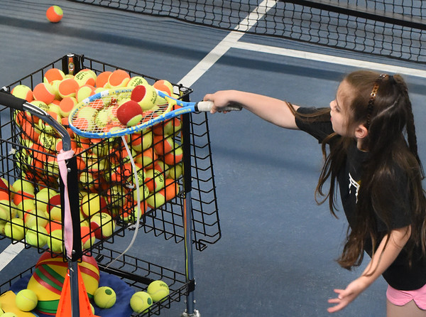BRYAN EATON/Staff photo. Bentlee Dragon, 5, dutifully helps out putting tennis balls back into the cage.