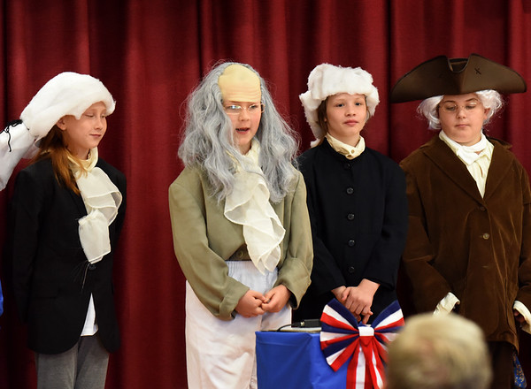 """BRYAN EATON/Staff photo. Cashman Elementary School third-graders put on the musical play """"The British Are Coming"""" re-enacting some historical events leading up to the Bill of Rights in a performance for parents at the Amesbury school on Wednesday morning. Presenting one scene are, from left, Patriots Faith Mainville, Lucas Zepf as Ben Franklin, Julliana Nocifora and Greg Harris."""