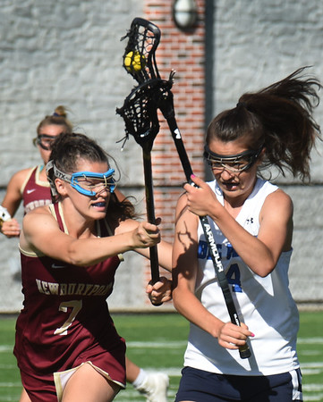 BRYAN EATON/Staff Photo. Lily Troupe knocks the ball from Swampscott's Elizabeth Green.