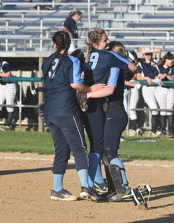 JIM VAIKNORAS/Staff photo Triton Players Bridget Sheehan (#3), Emily Karvielis, (#19) hug pitcher Katharine Quigley after their victory over Arlington Catholic at Martin Field in Lowell..