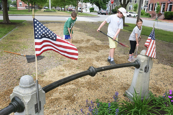 BRYAN EATON/Staff Photo. Imre Eigerman, 12, left, with sister Beatrix, 8, right, along with friend Max Donahue, 12, spread crushed stone around the statue of George Washington at the Bartlet Mall in Newburyport on Wednesday. The Eigerman's, and Donahue, were helping their mom, Andrea, who was on the Bartlett Mall Commission before the Newburyport Parks Department took over responsibilities to maintain the park and still likes to help care for the park.